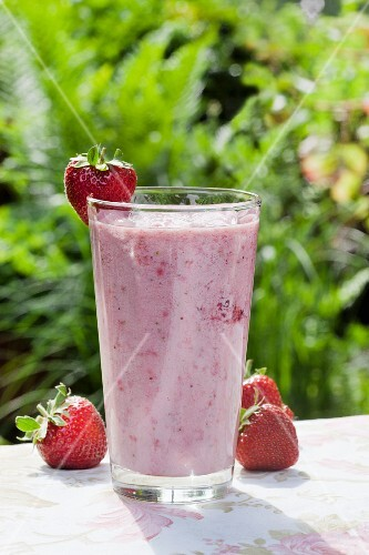 A strawberry smoothie and strawberries on a garden table