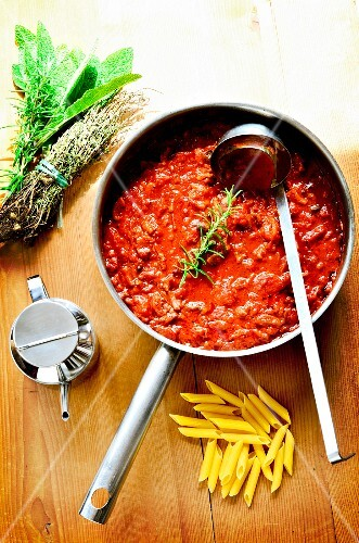 Bolognese sauce in a pan on a wooden board with penne pasta, herbs and olive oil