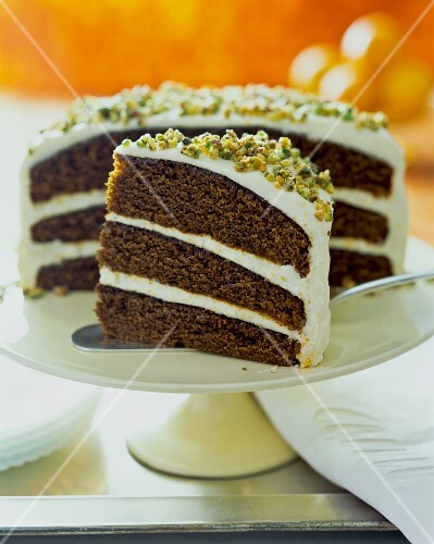 Chocolate pistachio cake, sliced, on a cake stand