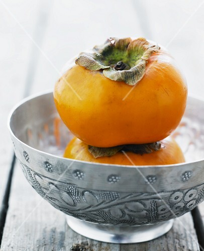 Two persimmons stacked on top of each other