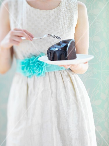 A woman in a white dress eating a slice of chocolate cake