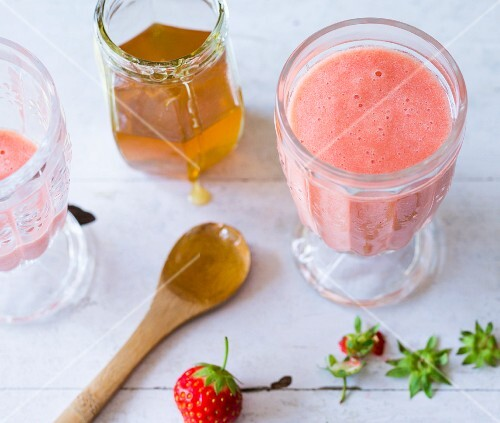 A strawberry smoothie made with pineapple and honey
