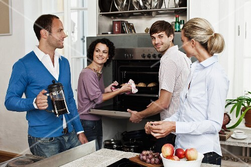 Two couples in the kitchen in front of an oven