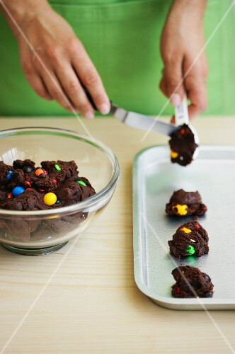 Chocolate biscuits with colourful chocolate beans being made