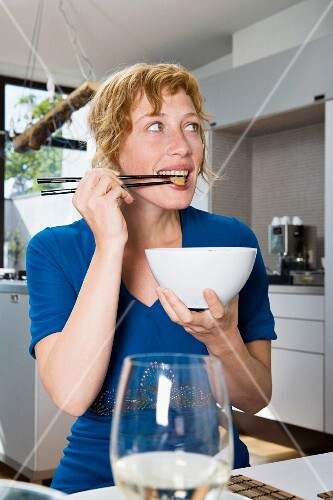 A woman eating a stir-fry with chopsticks in a kitchen