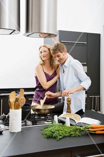 A couple cooking together in a kitchen