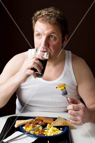 A stereotypical Englishman eating an English breakfast and drinking a pint
