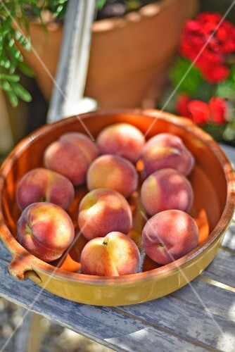 A bowl of fresh peaches on a garden chair