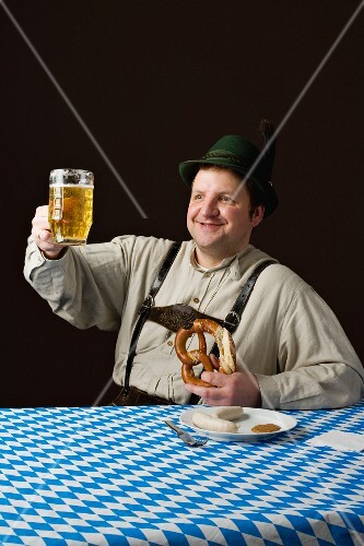 A stereotypical German man wearing lederhosen and eating a pretzel and white sausage with beer