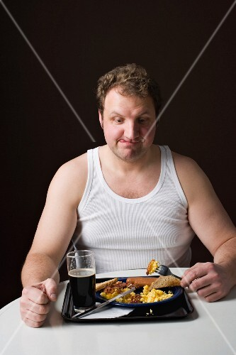 A stereotypical Englishman eating an English breakfast