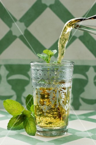 Peppermint tea being poured into a glass