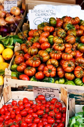 Various tomatoes in crates at a market