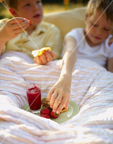 Two boys eating pancakes with strawberries for breakfast in bed in a field