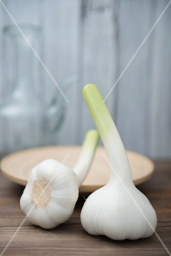 Two fresh garlic bulbs on a wooden table