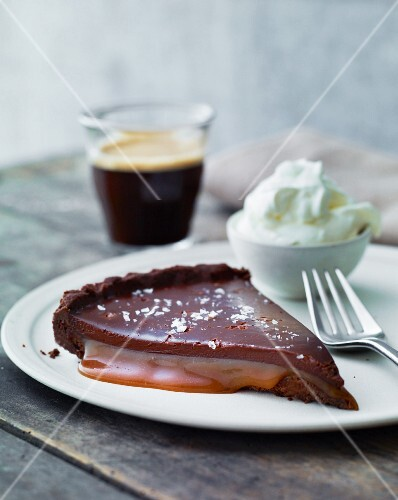 A slice of chocolate cake with caramel sauce and cream