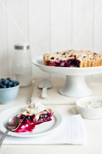 A slice of blueberry pie with cream on a plate with the rest of the pie on a cake stand in the background