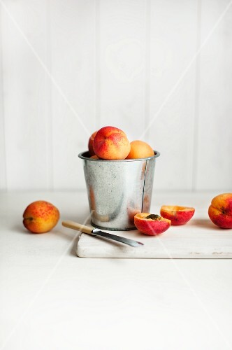 Apricots in a metal container and next to it, one halved