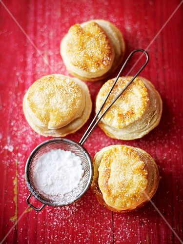 Mince pies and a sieve of icing sugar on a red wooden surface