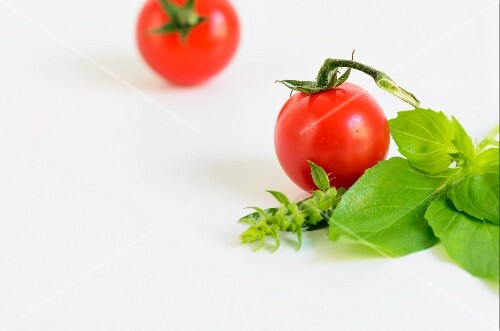 Two tomatoes and fresh basil