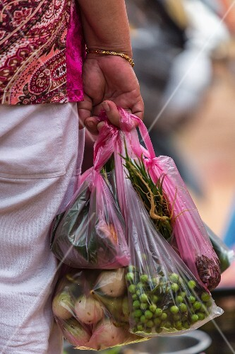 A woman carrying plastic bags of vegetables at a market (Vientiane, Laos)