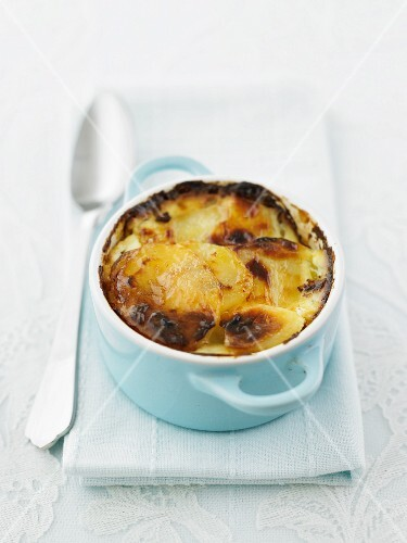 Potato gratin in a light blue ceramic dish