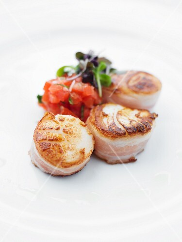 Three fried scallops wrapped in bacon with tomato tartar and shiso cress