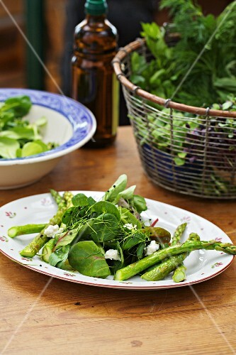 A salad made with green asparagus, spinach and fresh herbs