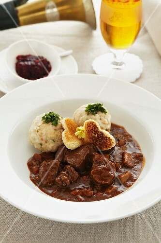 Young venison ragout with bread dumplings and cranberries