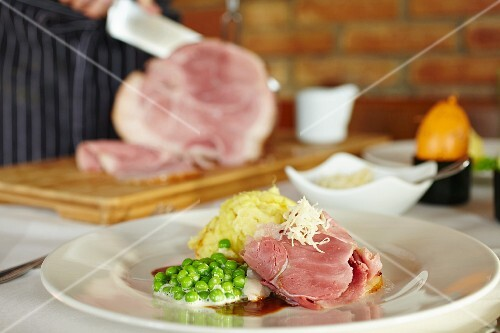 Glazed leg of ham with mashed potatoes and mint peas