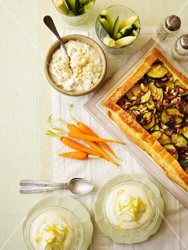 An arrangement of raw vegetables, a dip, courgette tart and lemon cream