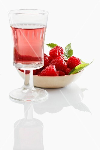 A glass of raspberry liqueur in front of a bowl of fresh raspberries