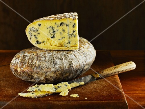 Barkham Blue blue cheese from England with a knife on a wooden board