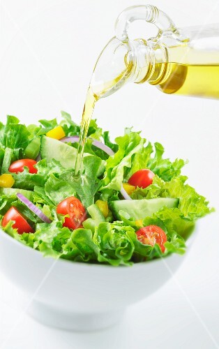 Oil being poured onto a salad of cherry tomatoes, cucumber, peppers and onions