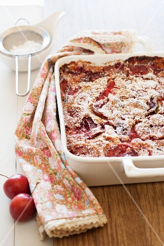Freshly baked clafoutis with plums in a baking dish