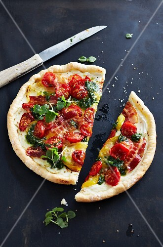 Pizza with pesto, tomatoes, bacon and herbs