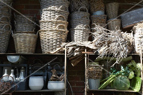 Wicker baskets and containers on a shelf with woven roots at the side