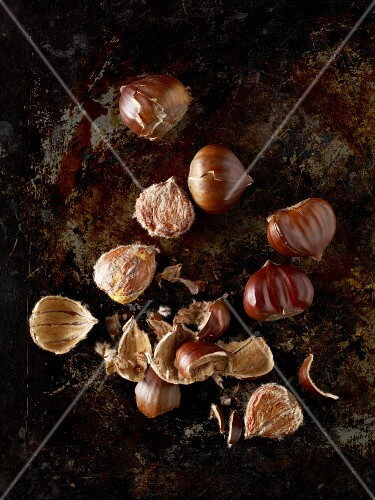 Roast chestnuts, some shelled, on a baking tray