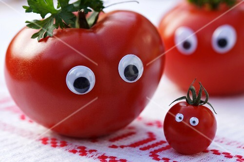 A tomato family with eyes on a rustic tablecloth