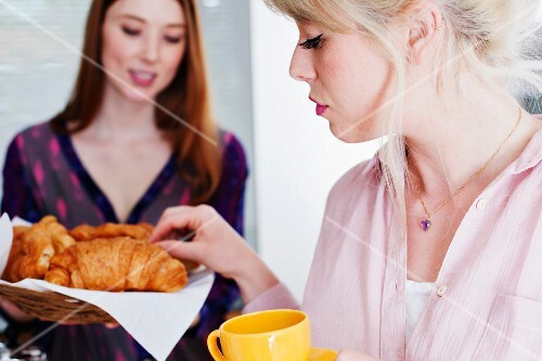 Young women with croissants in a kitchen