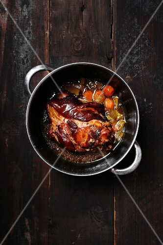 Braised pork knuckles with carrots in a saucepan