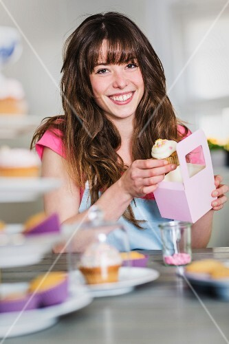 A woman packing homemade cupcakes into gift boxes