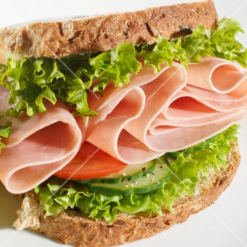 A ham sandwich with cucumber, tomato and lettuce