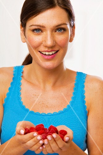 A young brunette woman holding raspberries in both hands