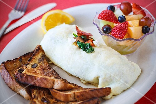 A bacon, spinach and feta omelette served with toast and fruit salad