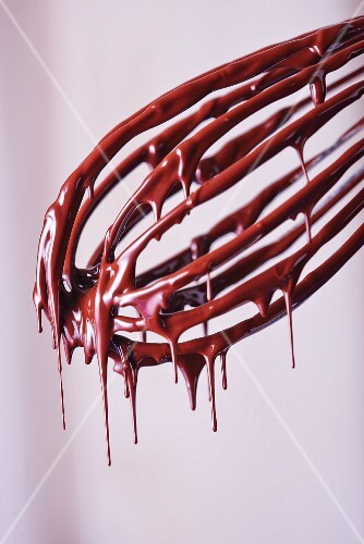 Liquid chocolate dripping from a whisk
