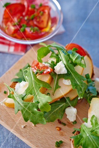 Slices of bread topped with rocket, pears, feta and tomatoes