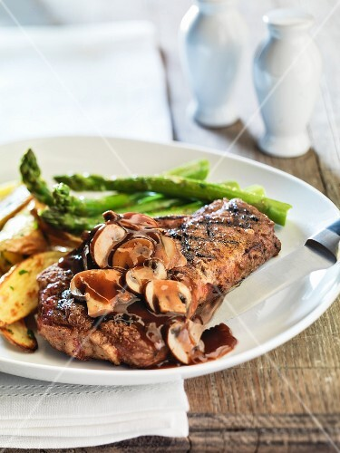 Strip steak with asparagus, mushroom sauce and potatoes