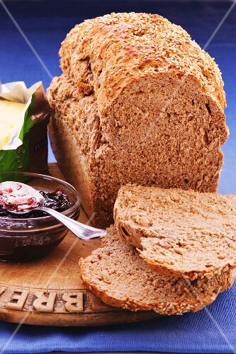 A loaf of bread with brewers grains, two slices cut off, next to butter and jam