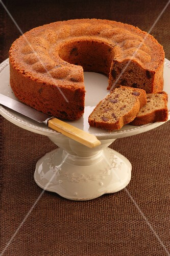 Date and coffee cake, sliced, on a cake stand