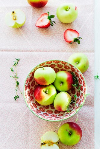 An arrangement of apples in a bowl with strawberries